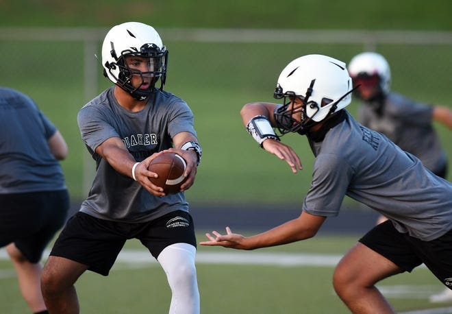 Quaker Valley High School quarterback Patrick Cutchember, left, works on handoffs with Gavin Eshenbaugh during practice on Sept. 3.