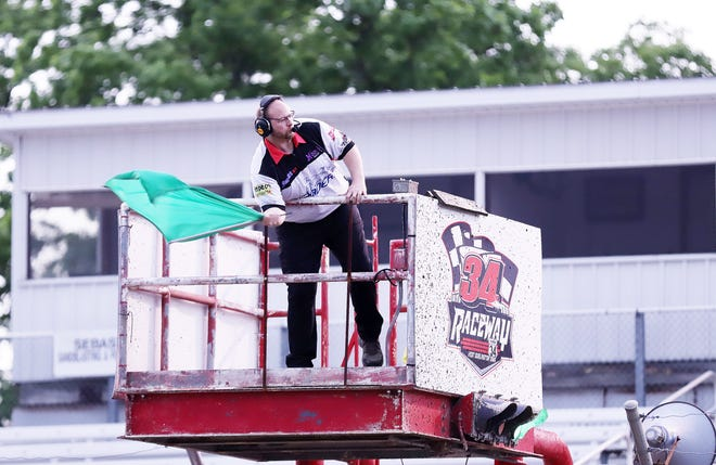 Burlington native Rodney Bliesener waves the green flag at 34 Raceway earlier this season. Bliesener, a former racer, crewman and wrecker driver, is in his fourth season as a flagman.