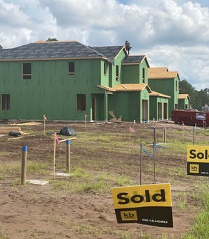 A builder works on the roof of a Meadows at Oakleaf home behind the Oakleaf Town Center in Jacksonville on Labor Day. The housing market has been so robust during the pandemic that there aren't even enough houses to keep up with the demand, according to the Northeast Florida Association of Realtors.