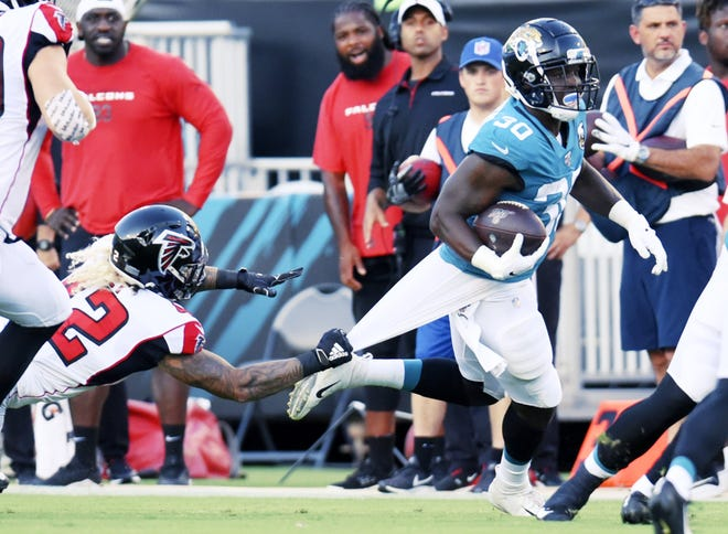 Jaguars running back Ryquell Armstead (30) runs for a first down with Falcons linebacker Duke Riley (42) in pursuit during the 2019 preseason.