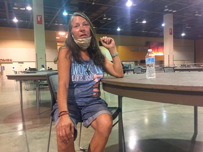 Lena Stewart, 57, receives a water bottle at the heat respite center at the Phoenix Convention Center recently. The area can accommodate up to 250 people and since opening in late May officials have recorded more than 17,000 visits.