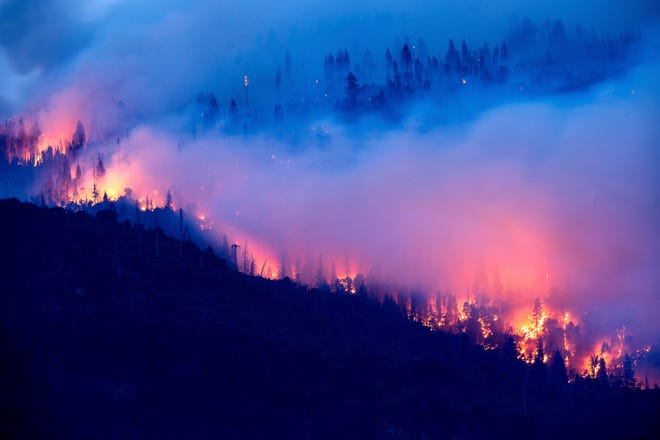 The Creek Fire burns along a hillside in the Cascadel Woods community of Madera County, Calif., on Monday, Sept. 7, 2020.