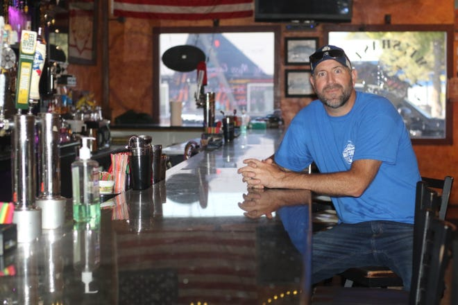 Kris Watson sits at the empty bar at Watson's Vets Club on Sept. 7, 2020.