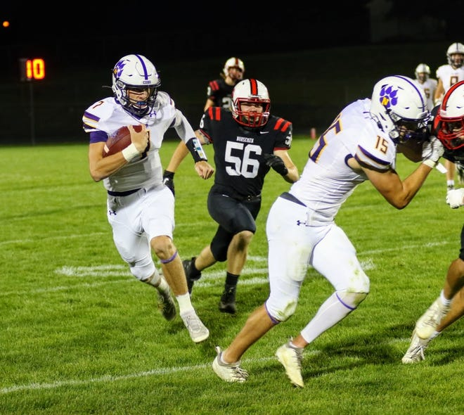 Nevada quarterback Brayden Bottorf follows the block of Ayden Rhodes (15) on a run during the Cubs' 63-6 victory over Roland-Story Friday in Story City. Bottorf threw for 190 yards and a touchdown and ran for 48 yards and another score to help the Cubs move to 2-0.