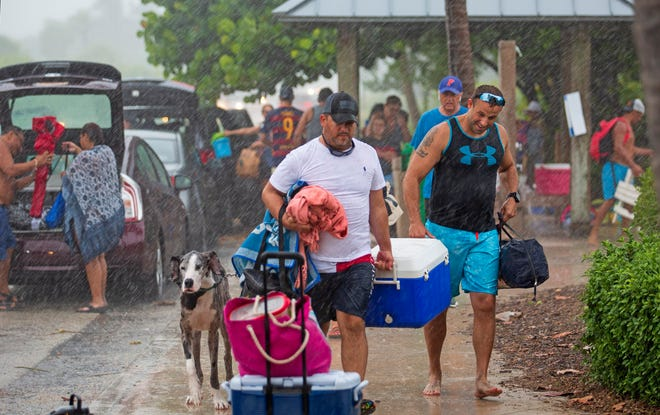 Beachgoers flee the shore in Jupiter as rain moves inland off the ocean Sunday afternoon, September 6, 2020. [LANNIS WATERS/palmbeachpost.com]