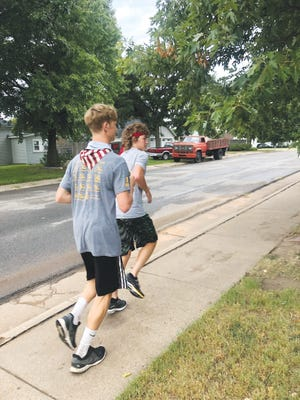 Pratt High School senior Kaiser Pelland and sophomore Kaden Barker are working on getting in shape for running during early morning practices, along with a strong-in-numbers Greenback team.
