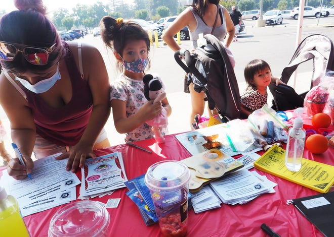 "Yovanna Pineda, 23, left, with her children Kat Pineda, 5, center, and Zola Pineda, 2, in a stroller, signs up to receive activity boxes for the children during Stockton Black Family Day event in front of Barnes & Noble Booksellers at Weberstown Mall. Normally on Labor Day, the community would be coming together for the annual Stockton Black Family Day event at Weber Point Events Center, but because of the pandemic, this year's event, in its 52nd year, was a virtual celebration spread over three days. ""Stockton Black Family Day is important because it is a part of Stockton's history, this has been going on for 52 years,"" said Fayette Reynolds, who has been active with the celebration for more than 30 years. ""It's a cultural celebration that has allowed us to bring the Black community together in a family-safe environment and provide programs items for kids, health screening and health information."" Additional information on virtual streaming, games and crafts is offered at stocktonblackfamilyday.com."