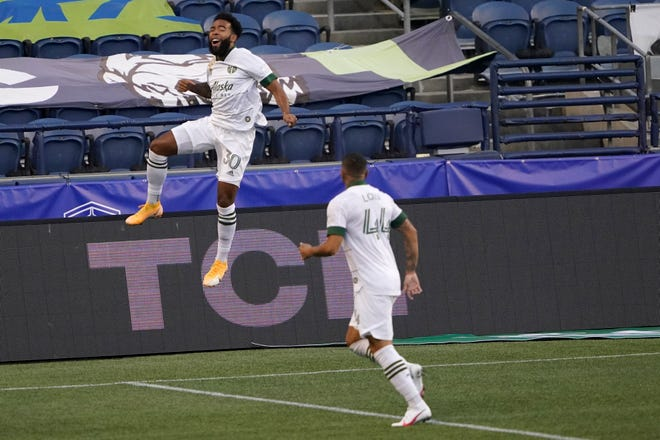 Portland Timbers midfielder Eryk Williamson, left, leaps in celebration with Marvin Loria (44) after Williamson scored a goal against the Seattle Sounders during the first half of an MLS soccer match, Sunday, Sept. 6, 2020, in Seattle. (AP Photo/Ted S. Warren)