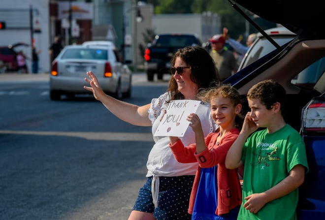 "Showing a ""Thank You"" sign to parade entries passing through the town square, left to right Kate Mullen with Jackie, 9-years-old, and Wyatt, 11-years-old, during the much downsized 134th Annual Labor Day Association Parade in downtown Princeton Monday morning, September 7, 2020."