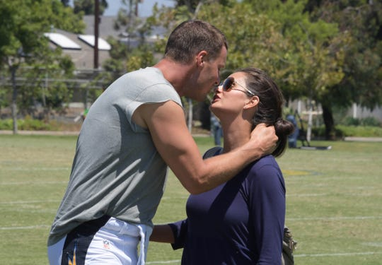 Then with the Los Angeles Chargers, quarterback Philip Rivers kisses wife Tiffany during practice on Aug. 17,