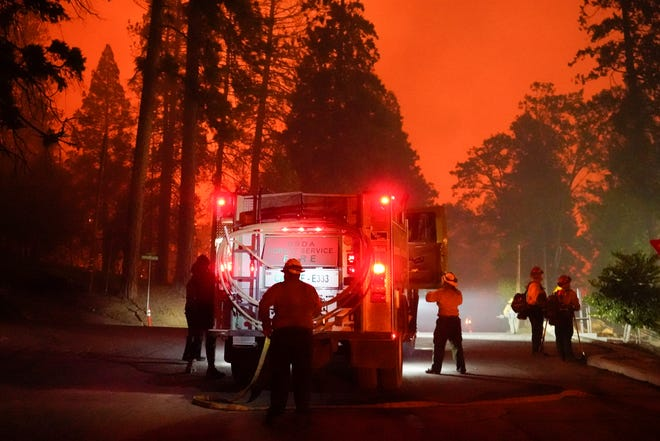 Firefighters stage near a Southern California Edison power station to protect it from the advancing Creek Fire, Sunday, Sept. 6, 2020, in Big Creek, Calif.