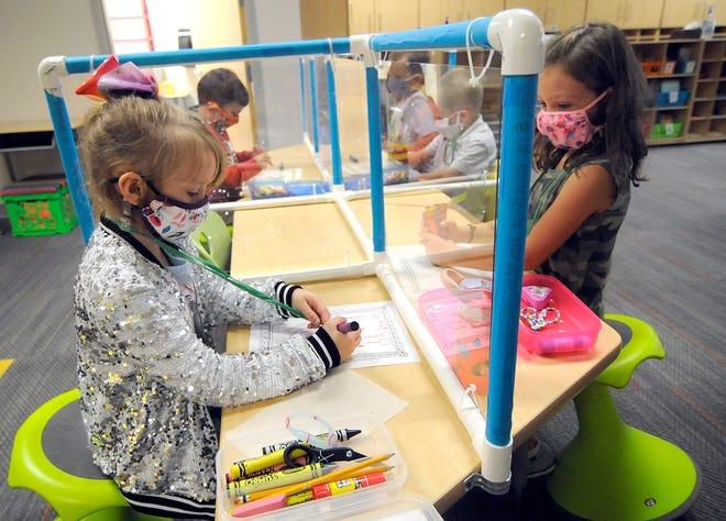 Reagan Elementary School kindergarten students Amiya Piatt (left) and Peyton Reynolds work on an art project during the first day of school, Sept. 8.
