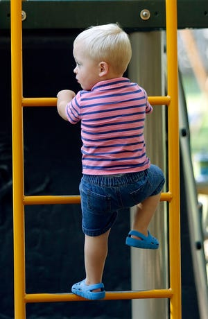 Maddox Dew climbs on the playground equipment at Brookside Park during a visit to the park with his mother and brother on Tuesday.