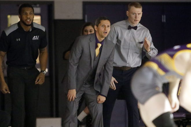 Former Ashland University wrestling Josh Hutchens (center) shouts from the edge of the mat during the match against University of Pitt-Johnstown on Dec. 7, 2019 at Kates Gymnasium.