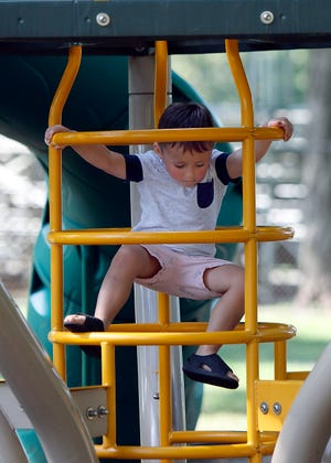 Jax Dew climbs on the playground equipment at Brookside Park during a visit to the park with his mother and brother on Tuesday.