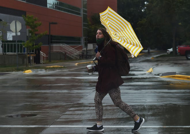 A student of Iowa State University shields herself with an umbrella as the wind blows the Umbrella inside out during the sprinkle at the university central campus Tuesday, Sept. 8, 2020, in Ames, Iowa.
