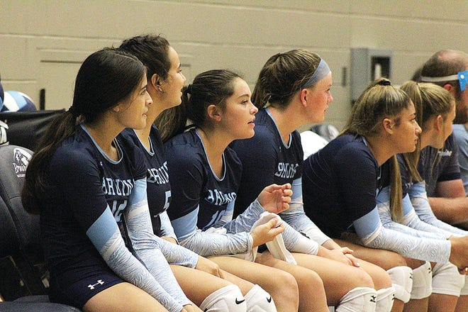 Bartlesville High School volleyball players, including some starters taking a breather, look on during early-season action at the Bruin Fieldhouse.