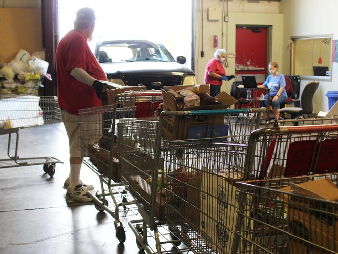 Staff and volunteers for Mary Martha Outreach work the drive-through food giveaway Tuesday.