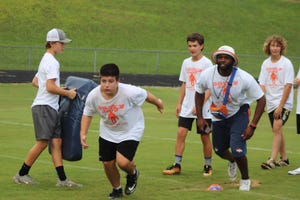 Josh Bush (second from right) leads campers in a drill in 2019. Bush spent four years in the NFL with the New York Jets and Denver Broncos. [Photo by Adriana Tuttle]