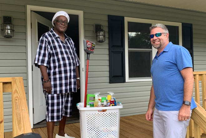 Vinson Lewis (left) stands on the front porch of a newly built house by the Lexington Housing Community Development Corporation. Lewis recently purchased the property with the help of the organization.