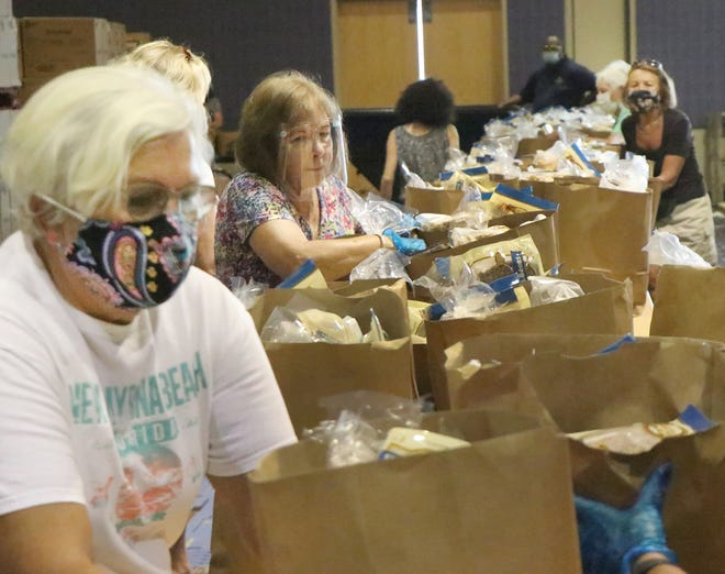 An army of volunteers fill bags with food for Halifax Urban Ministries, Tuesday September 8, 2020 inside the Ocean Center.