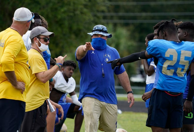 A masked Scott Wilson directs a recent Mainland High football practice as he, his staff and his players get used to the safety procedures in place to combat the spread of the coronavirus. The Buccaneers are expecting to be competitive again this season, which finally arrives Friday night after many delays caused by the pandemic.