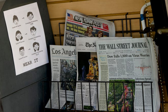"""A sign reads """"Wear it,"""" posted next to a newspaper rack at a coffee shop in the Venice Beach area of Los Angeles Friday, June 12, 2020. Stocks rose broadly on Wall Street Friday, recouping some of their losses a day after the market had its biggest rout since mid-March. (AP Photo/Damian Dovarganes)"""