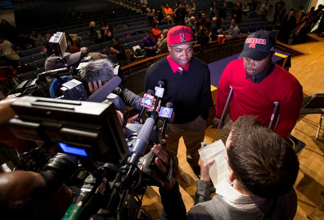 The Davis twins, Khalil, left, and Carlos, speak with the media after signing their letters of intent for the University of Nebraska during signing day at Blue Springs High School's Performing Arts Center in February 2014.