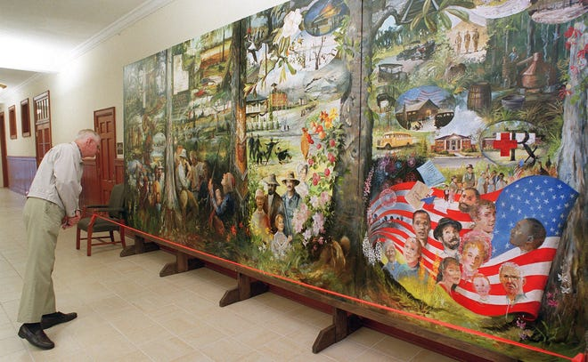 The mural showing facets of Baker County's history  has drawn attention for  years. In this 2002 photo, a Jacksonville man stopped at the Baker County Courthouse on his way home from Lake City with his wife to examine it.
