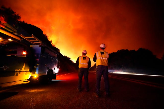 Pacific Gas and Electric workers stand along Highway 168 as the Creek Fire advances Tuesday, Sept. 8, 2020, near Alder Springs, Calif.