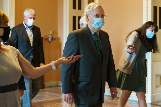 Senate Majority Leader Mitch McConnell, R-Ky., center, walks to his office from the Senate floor Tuesday on Capitol Hill in Washington.