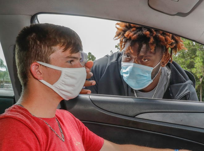 Cohen Bogue, a sophmore, has his temperature checked by graduate student Jaquez Dickerson at the entrance to Warner University in Lake Wales on Tuesday. Warner University recently began fall classes with protective measures