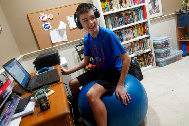 FILE - In this Aug. 31, 2020, file photo, Andrew Burstein, 13, logs onto 8th grade class with Don Estridge High Tech Middle School from his home in Delray Beach, Fla., during the first day back for Palm Beach County Schools. Burstein said it took about an hour to log into school, but after the delay he had no issues.