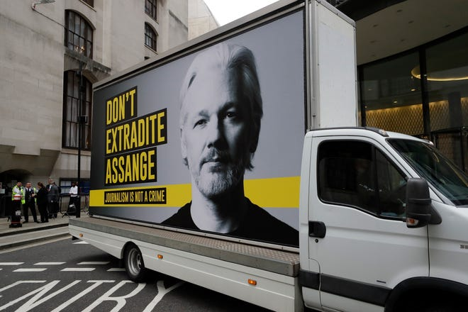 A billboard truck depicting Julian Assange drives past the Central Criminal Court Old Bailey in London on Tuesday. Lawyers for WikiLeaks founder Julian Assange and the U.S. government were squaring off in a London court this week at a high-stakes extradition case delayed by the coronavirus pandemic. American prosecutors have indicted the 49-year-old Australian on 18 espionage and computer misuse charges over Wikileaks' publication of secret U.S. military documents a decade ago. The charges carry a maximum sentence of 175 years in prison.