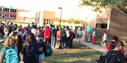 Masked Pratt students gather outside Liberty Middle School before entering each morning for school.