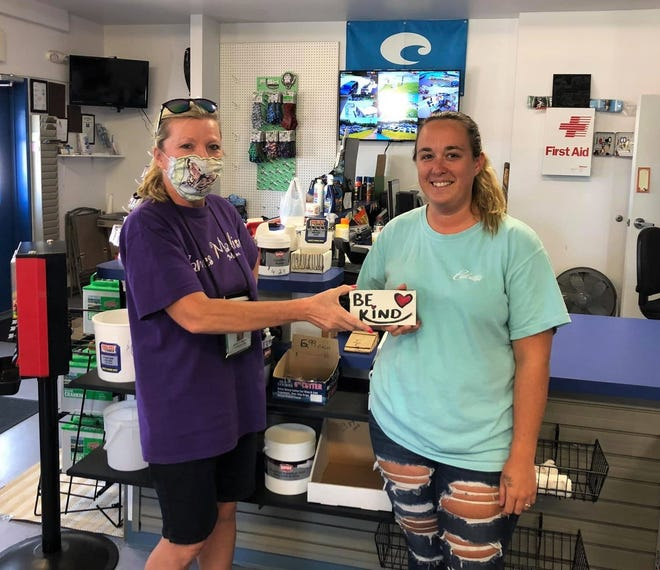 "On the left, the Social Butterfly Kristi K. Higgins presents Fish Tales 2 team member Courtney Ellis of Hopewell with a 'Be Kind' sign at the Hopewell Marina on September 7, 2020. ""My dad who owns this place and is a battalion chief is all about kindness and will love it,"" said Ellis."