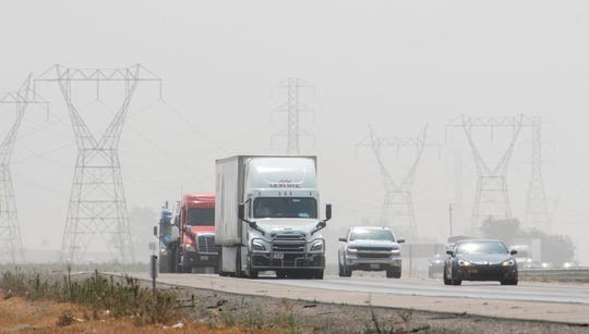 Traffic drives Interstate 5 near Highway 12 through dust and devastating smoke blown by north winds.