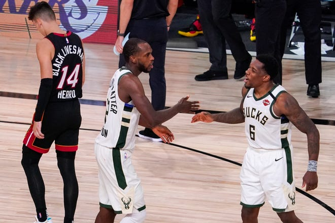Milwaukee's Khris Middleton and Eric Bledsoe (6) celebrate as Miami's Tyler Herro walks off the court after the Bucks downed the Heat 118-115 in Sunday's playoff game in Lake Buena Vista, Fla. The Heat lead the series 3-1 entering Tuesday night's game. (AP Photo/Mark J. Terrill)