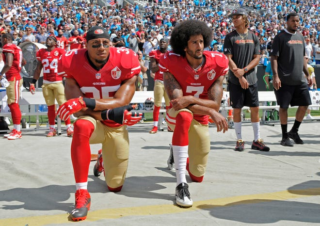 San Francisco 49ers players Eric Reid, left, and Colin Kaepernick kneel during the national anthem before a Sept. 18, 2016, game against the Carolina Panthers in Charlotte, N.C. (AP Photo/Mike McCarn)