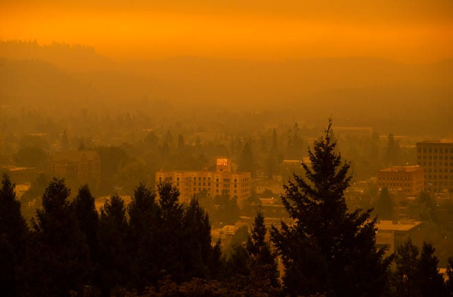 The Eugene Hotel sign shines through a dense layer of smoke as seen from the top of Skinner Butte in Eugene on Tuesday as smoke from wildfires burning in the state clogs the sky.