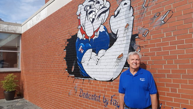 Dennis Brechner stands next to a mural of the Terry Sanford High School bulldog that he painted.