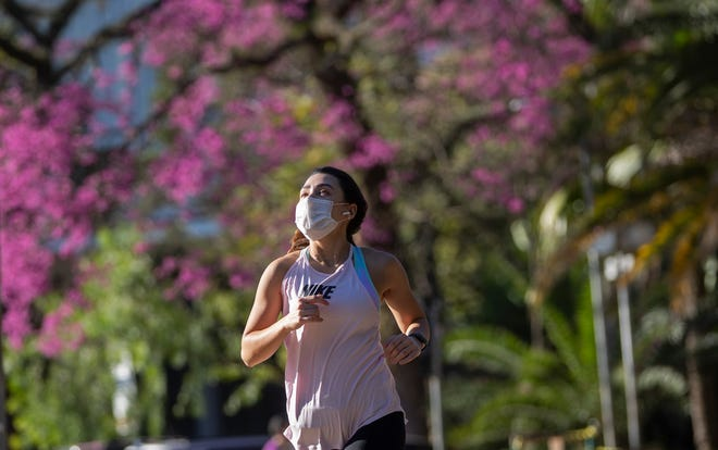 A woman jogs while wearing a mask.