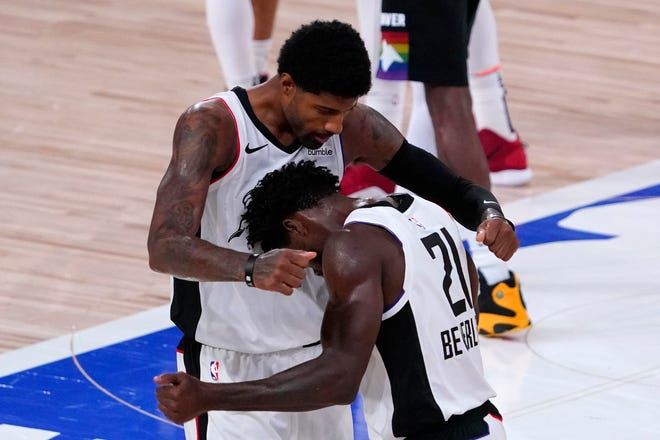 Los Angeles Clippers' Patrick Beverley, right, celebrates with Paul George after beating the Denver Nuggets on Monday, Sept. 7, 2020, in Lake Buena Vista, Fla.