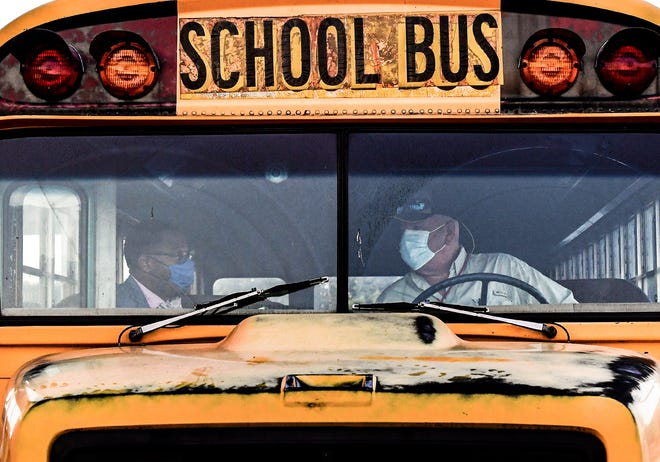 Glenview Middle School Prinicipal Leonard Galloway, left, talks with bus driver Frank Dobbs during the first day of school for Anderson School District Five in Anderson, S.C. Tuesday, September 8, 2020.