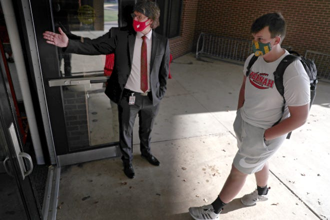 Chad Buboltz welcomes students on the first day of school at Neenah High School on Tuesday, Sept. 1, 2020, 2020, in Neenah, Wis.