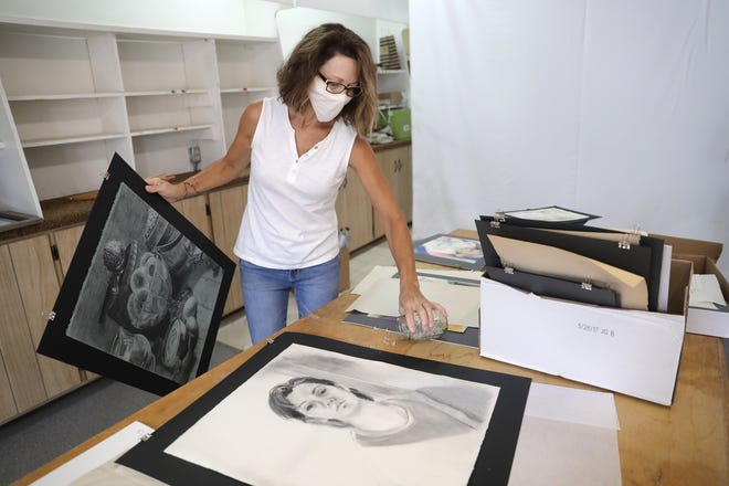 Shawn Boogaard sets up an exhibit of her sister's artwork at the former Coventry Glassworks on Aug. 22 in downtown Appleton. Boogaard's sister, Karri Knudtson, died in March after a battle with Huntington's disease.