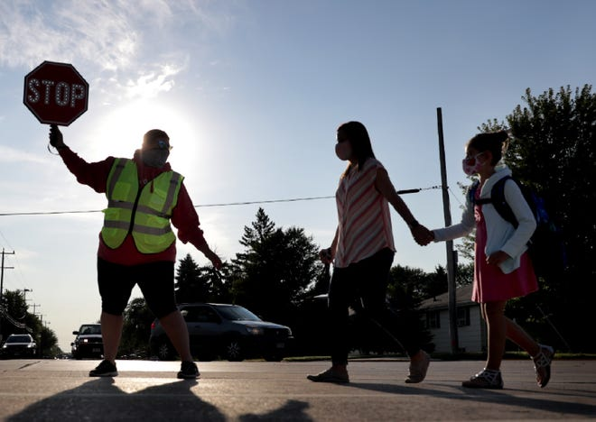 Crossing guard Shaina Fish stops traffic as students arrive at Tullar Elementary School on Tuesday, Sept. 1, 2020, in Neenah, Wis.