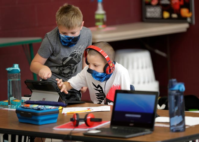 Braxton Compton, left, helps Deakon Nelson with a class project on Sept. 1 at the YMCA of Fox Cities' Classroom Connection program at Lincoln Elementary School in Appleton. Starting this week, the Appleton Area School District is bringing some of its most vulnerable populations of students back to classrooms for extra support while online learning continues.