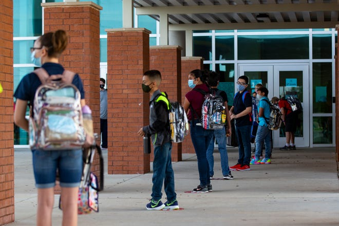 Students social distance as they wait to enter Adkins Middle School on the first day of in-person classes for Corpus Christi Independent School District schools on Tuesday, Sept. 8, 2020.