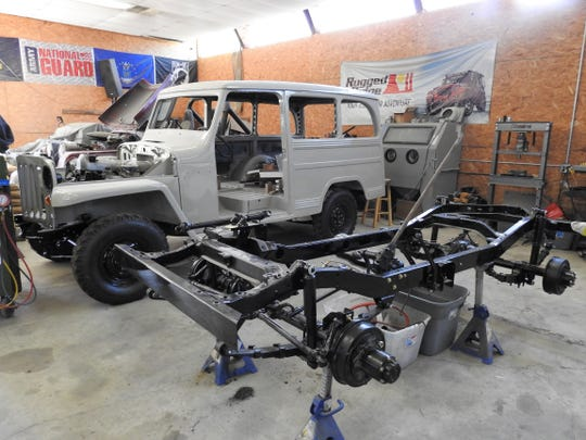 A gray 1961 Willys Wagon and a 1942 Willys Jeep frame are being worked on at Specialty Jeep of Coshocton, owned by Bruce Uher Sr. and Jr.